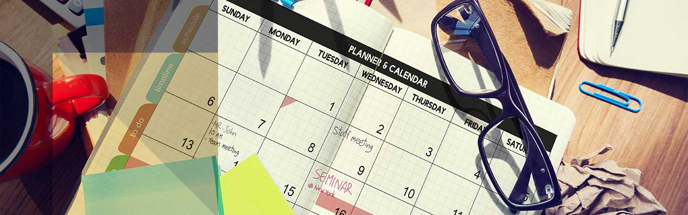 calendar on a table with glasses, cup, pin and writing pad